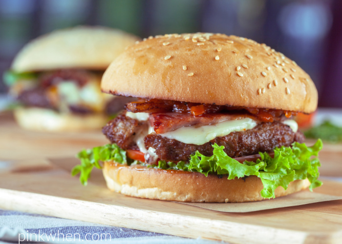 Air Fryer burger ready to eat and dressed on a bun with bacon, cheese, tomato, and lettuce.