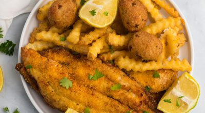 Overhead photo of a plate of catfish made in the air fryer with french fries, lemon wedges, and hush puppies.