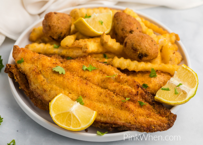 Air Fryer Catfish on a plate with french fries, hush puppies, and lemon wedges.