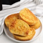 Cheese Toast made in the Air Fryer, on a white plate.