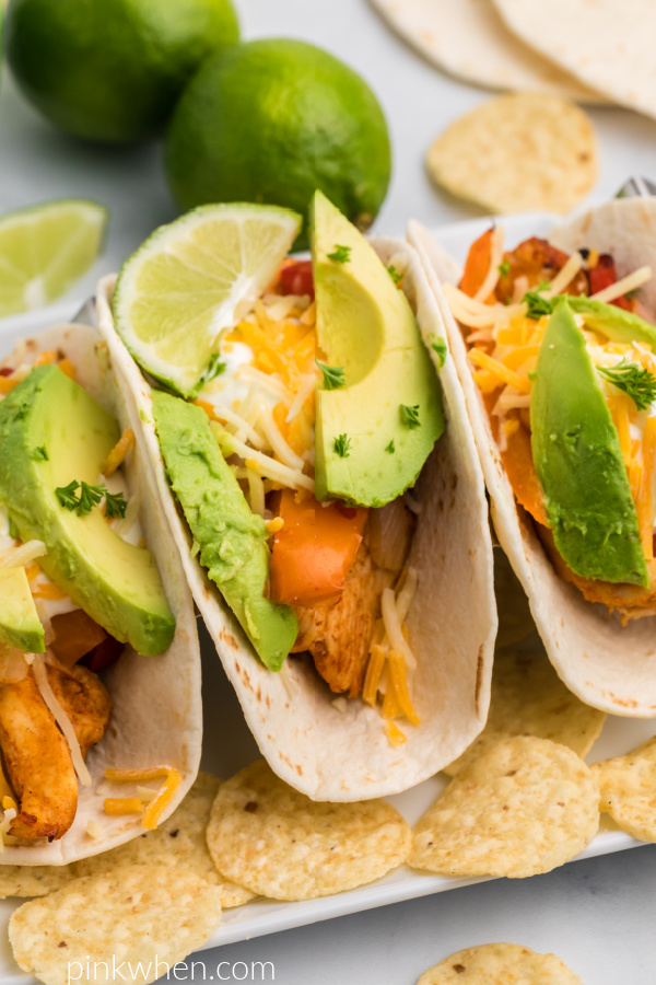 Close up photo of chicken fajitas on a plate with avocado, cheese, sour cream, and lime.
