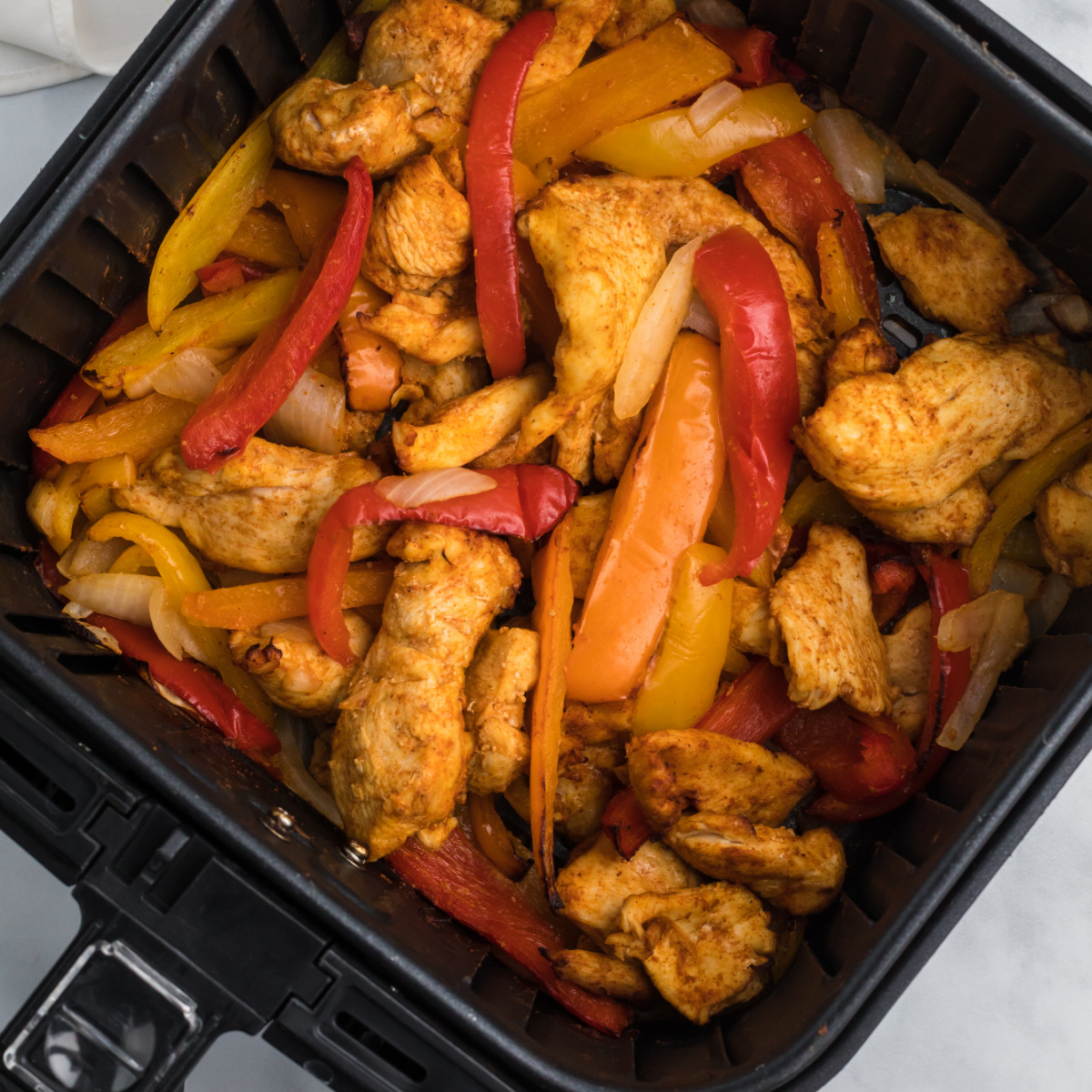Air Fryer Fajitas with chicken and vegetables in the air fryer basket.