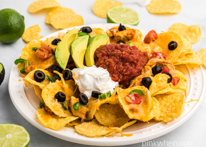 Air Fryer Nachos on a table surrounded by nachos and limes, and the nachos are piled onto a while plate. Air Fryer Nachos are also topped with sliced olives, sliced avocado, salsa, and sour cream.