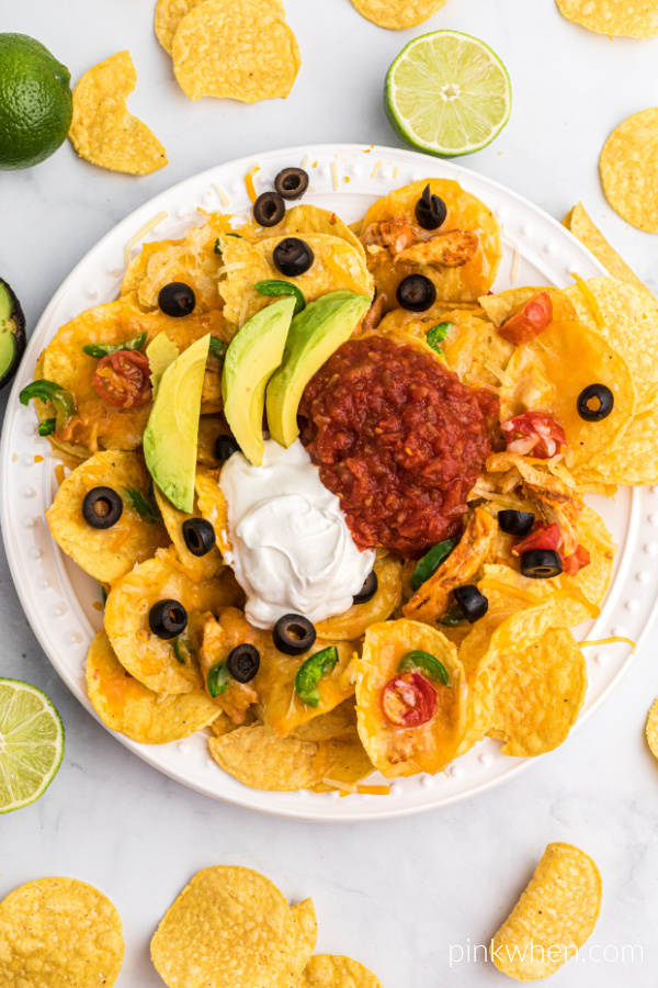 Air Fryer Nachos are layered onto a serving plate and topped with sliced olives, avocado slices, salsa, and sour cream.