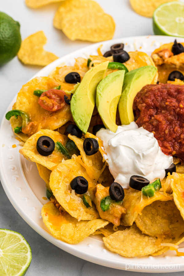Air Fryer Nachos on a white serving plate with sliced olives, salsa, sliced avocado, and a dollop of sour cream on top.