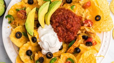 Air Fryer Nachos topped with sour cream, salsa, and avocado slices.