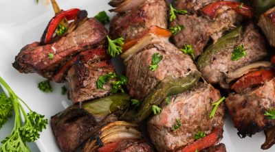 Steak Kabobs made in the Air Fryer and topped with fresh parsley. Served on a white plate.