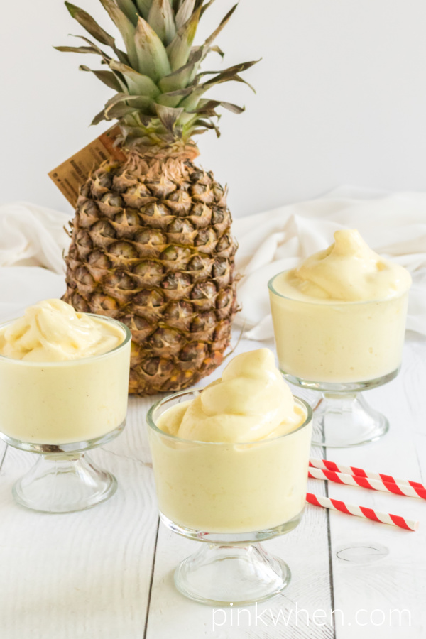 Three glasses with Dole Whip with red and white straw, pineapple in the background, and on a white table.