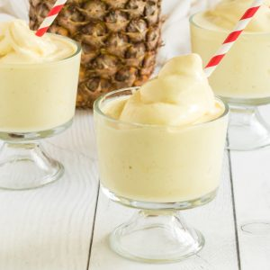 Dole Whip in clear glasses with red and white straws with pineapple in the background
