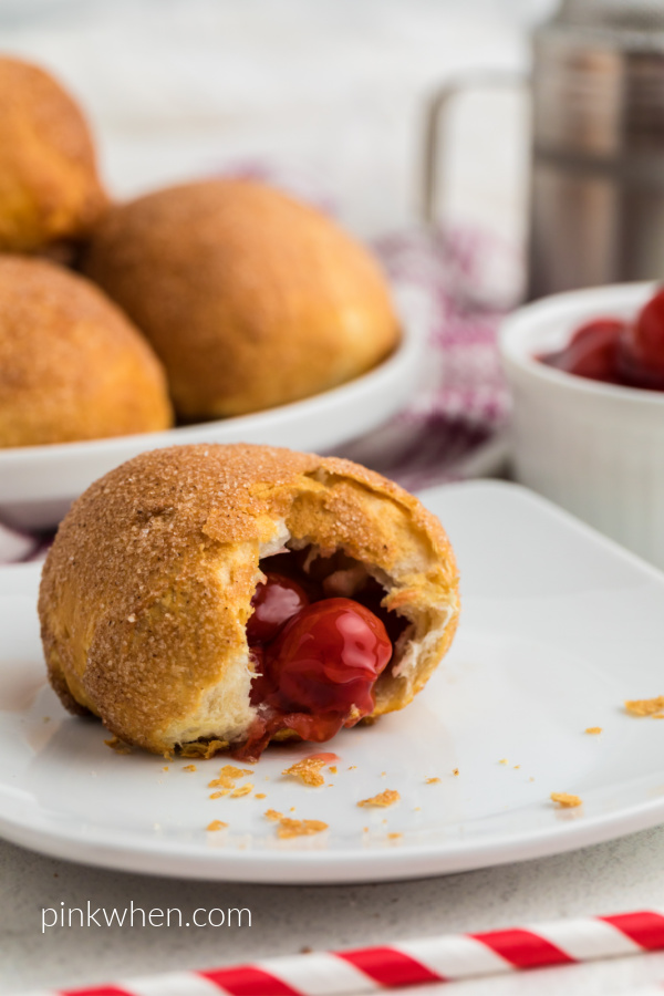 Air Fryer Cherry Pie Bomb on a white plate missing a bite with more cherry pie bombs in the background.
