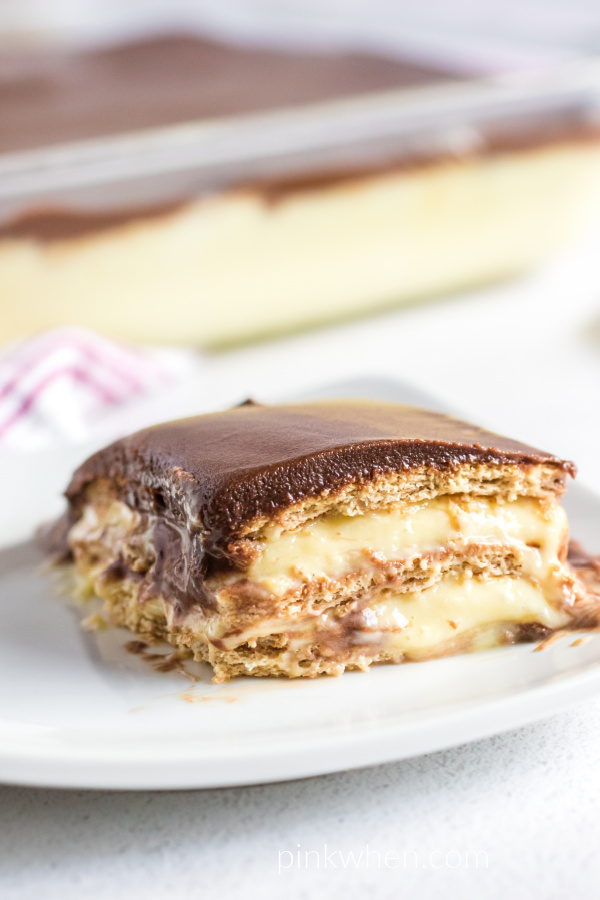 Slice of no bake chocolate eclair cake on a white plate ready to eat.