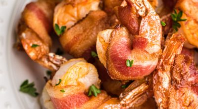 Bacon Wrapped Shrimp made in the air fryer on a white plate ready to serve.