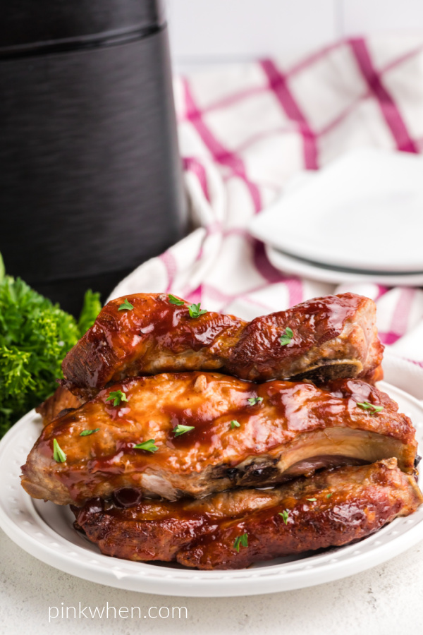 Country style ribs on a white plate with an air fryer in the background.