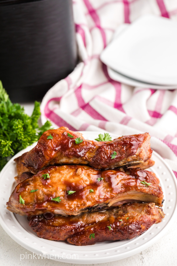 Air Fryer Country Style Ribs on a white plate smothers with barbecue sauce and topped with fresh parsley.