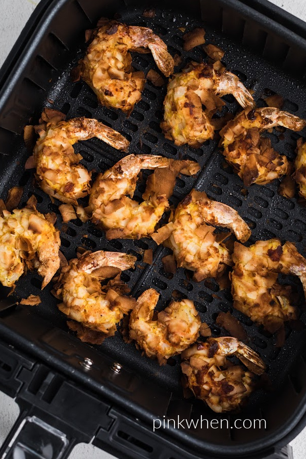 Coconut shrimp in the air fryer basket fully cooked.