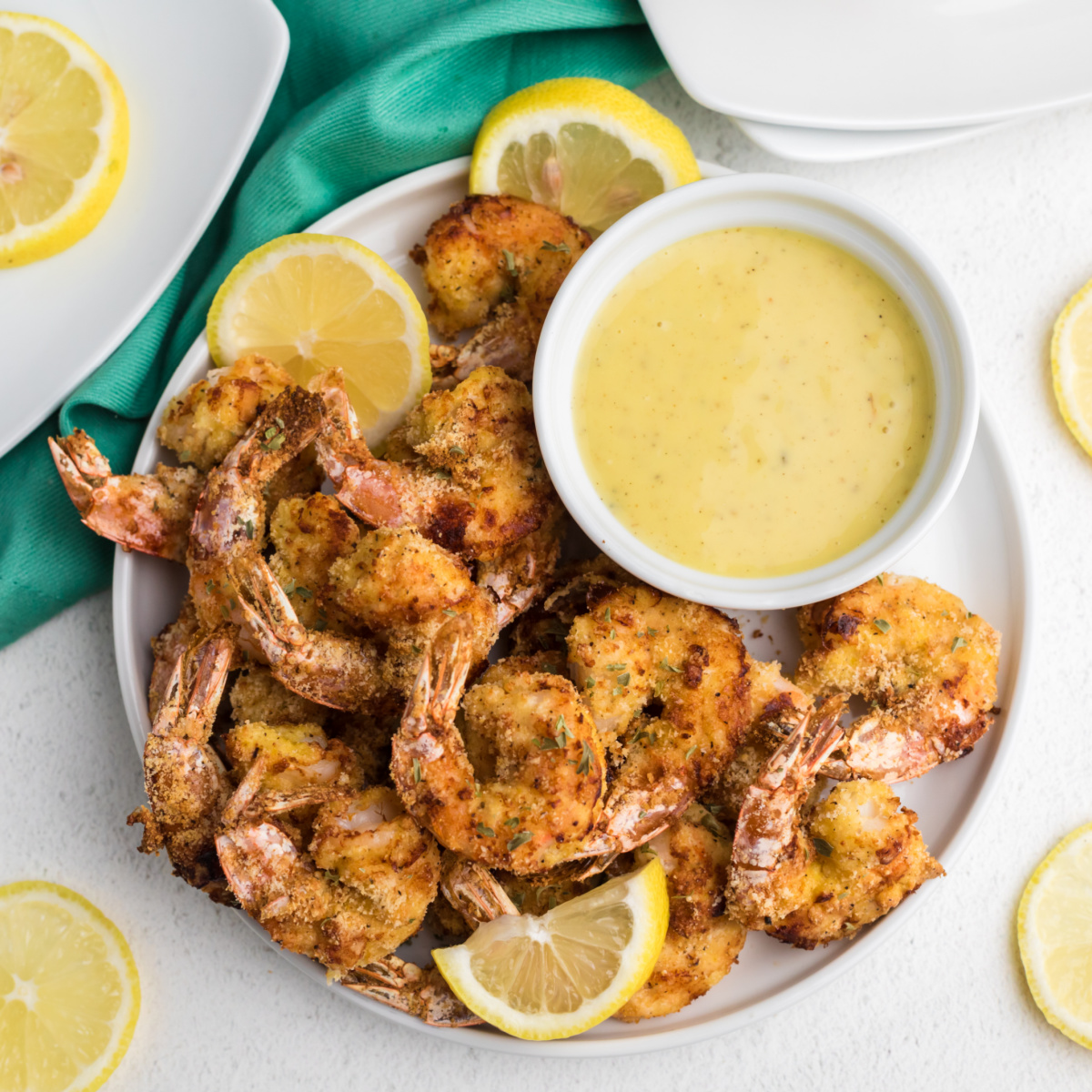 Air Fryer Fried Shrimp with lemon slices and serving sauce on a white plate.