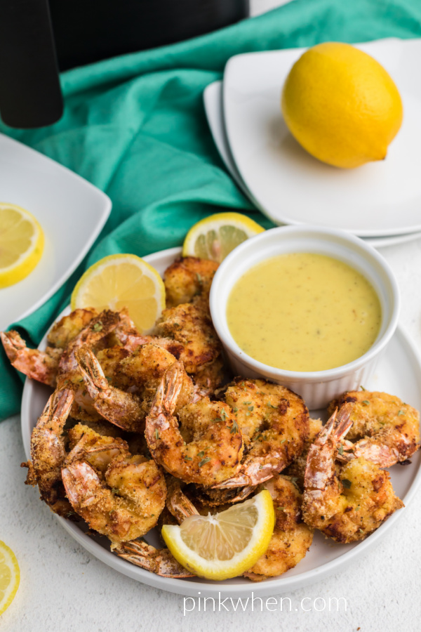 Fried shrimp made from the air fryer, served on a white plate with lemon slices and dipping sauce.