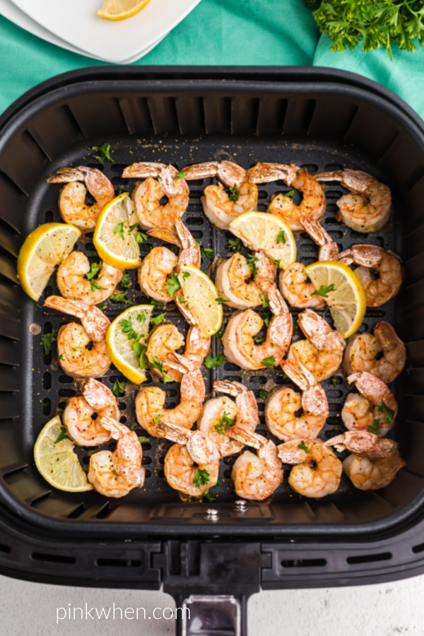 Lemon Pepper Shrimp and lemon wedges in the air fryer basket.
