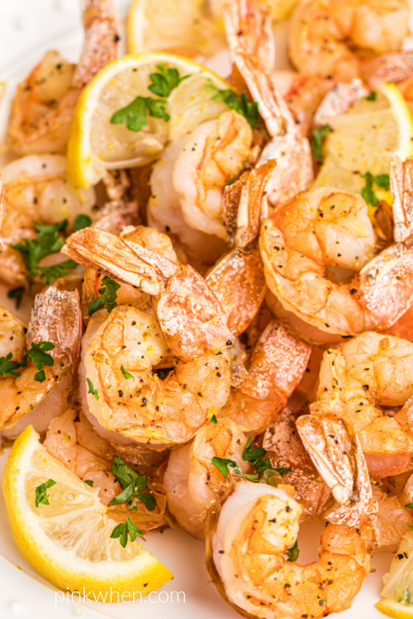 Air Fryer Lemon Pepper Shrimp fully cooked and on a white plate with lemon wedges and fresh parsley.