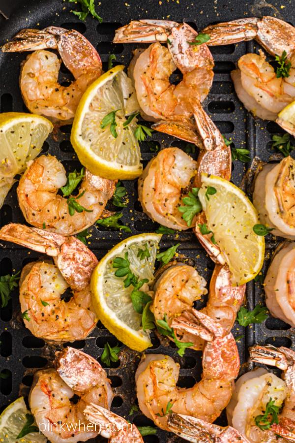 Air Fryer lemon pepper shrimp in the air fryer basket with lemon wedges and fresh parsley on top.