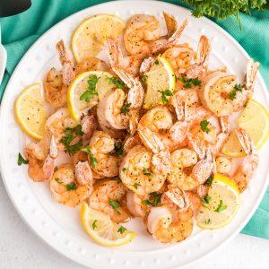 Overhead shot of air fryer lemon pepper shrimp on a white plate with lemon wedges and fresh parsley.