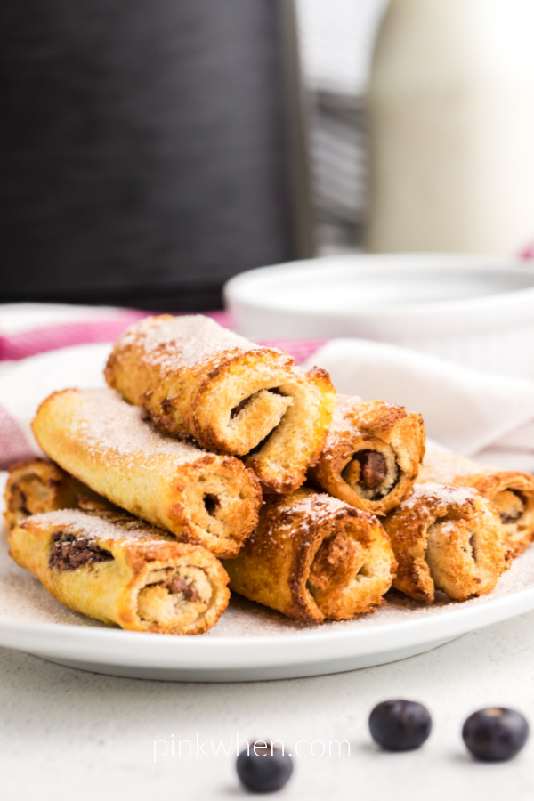 Nutella French Toast Roll Ups made in the air fryer on a white plate ready to serve.