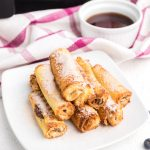 Nutella French Toast roll ups made in the air fryer and served on a white plate and topped with powdered sugar.