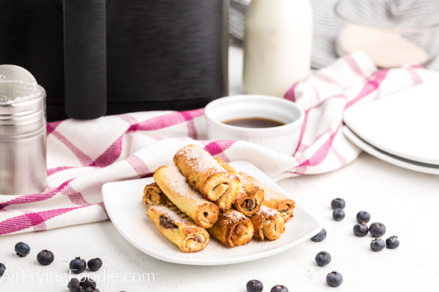 Air Fryer Nutella French Toast Roll Ups on a white plate and dusted with powdered sugar. Ready to eat!