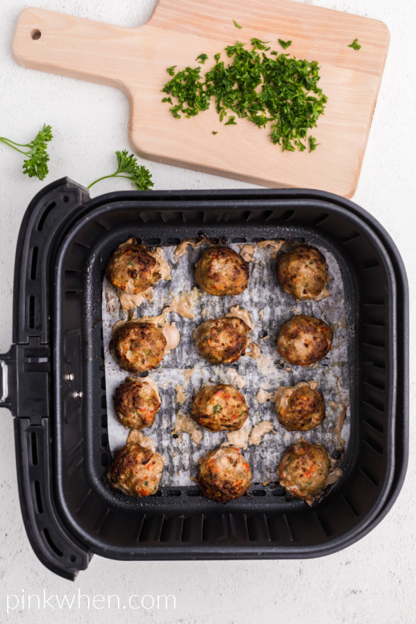 Turkey meatballs cooked and ready to serve in the basket of the air fryer.