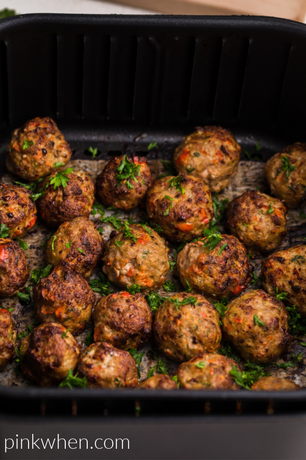 Turkey meatballs in the basket of the air fryer garnished with fresh parsley.