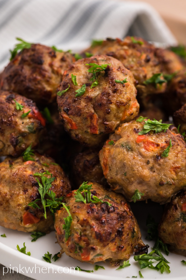 Air Fried Turkey meatballs on a white plate and garnished with fresh parsley.