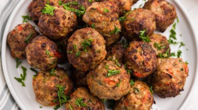 Air Fryer Turkey meatballs in a white plate garnished with fresh parsley.