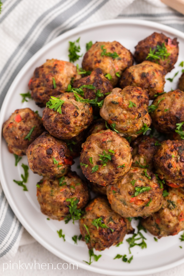 Air Fryer Turkey Meatballs on a white plate garnished with fresh parsley.