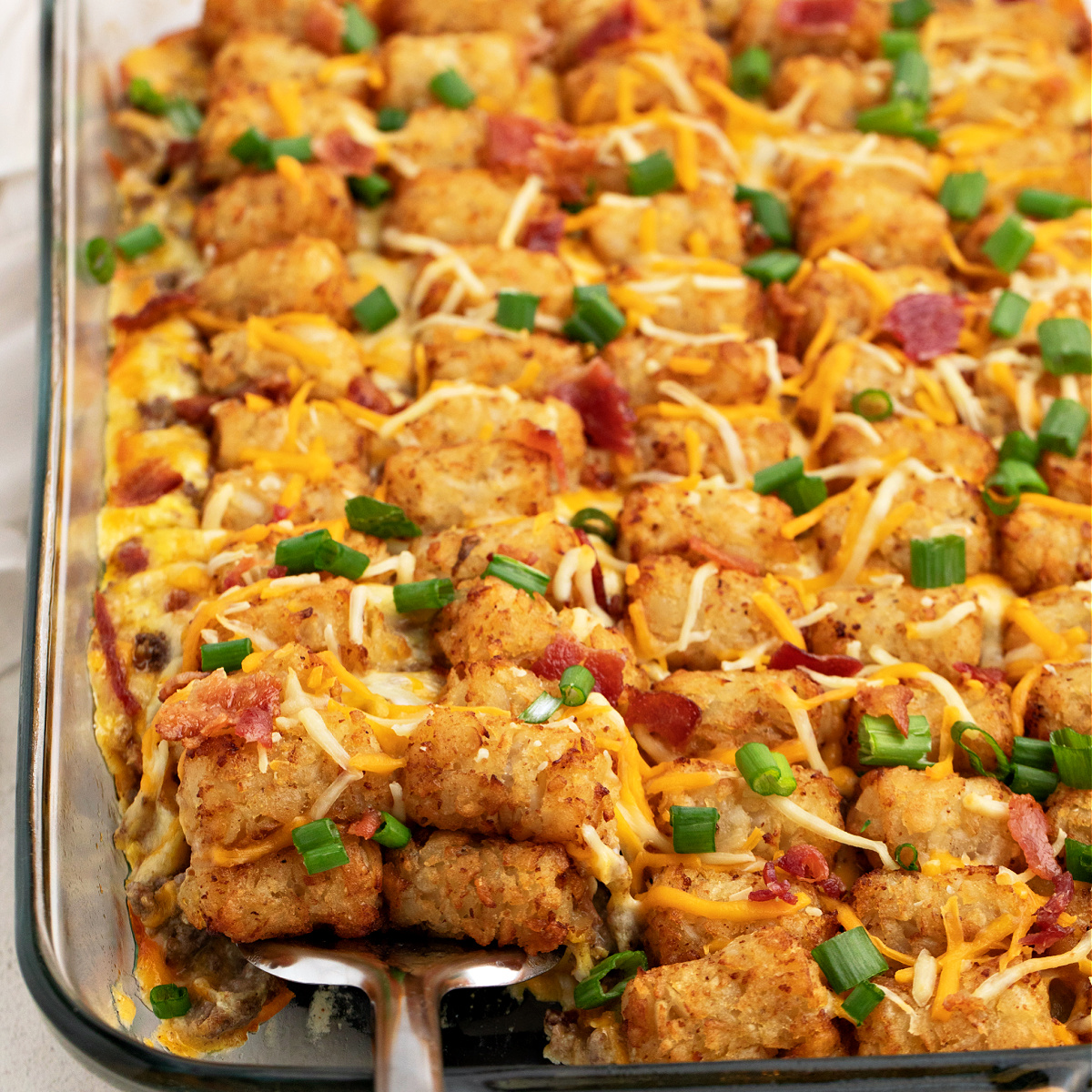 Bacon cheeseburger tater tot casserole being scooped from a casserole dish.