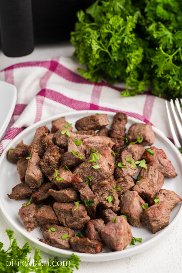Air Fried Garlic Butter Steak Bites on a white plate and garnished with fresh parsley.