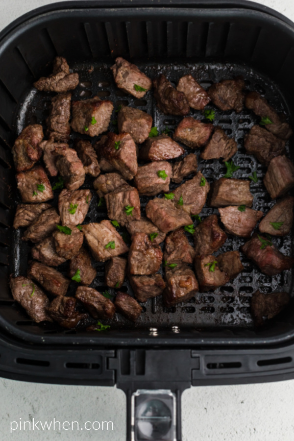 Cooked steak bites in the basket of the air fryer - topped with fresh chopped parsley.