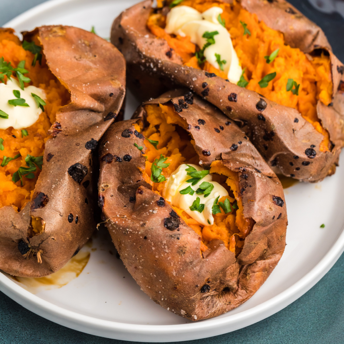 baked sweet potatoes made in the air fryer and topped with butter and fresh parsley.