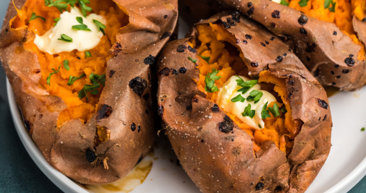 Sweet potatoes on a plate topped with butter and garnished with fresh parsley.