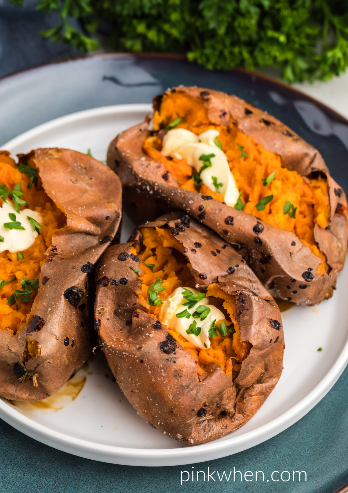 Air Fried Sweet Potatoes on a plate topped with butter and fresh parsley.