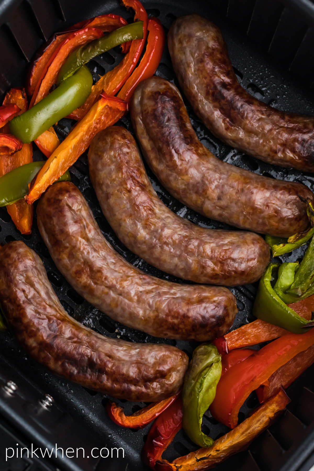 Cooked brats and bell peppers in the basket of the air fryer.