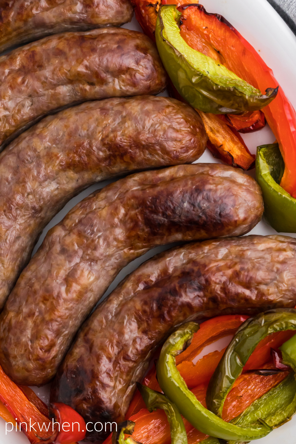 Close up photo of brats and peppers made in the air fryer and ready to eat.
