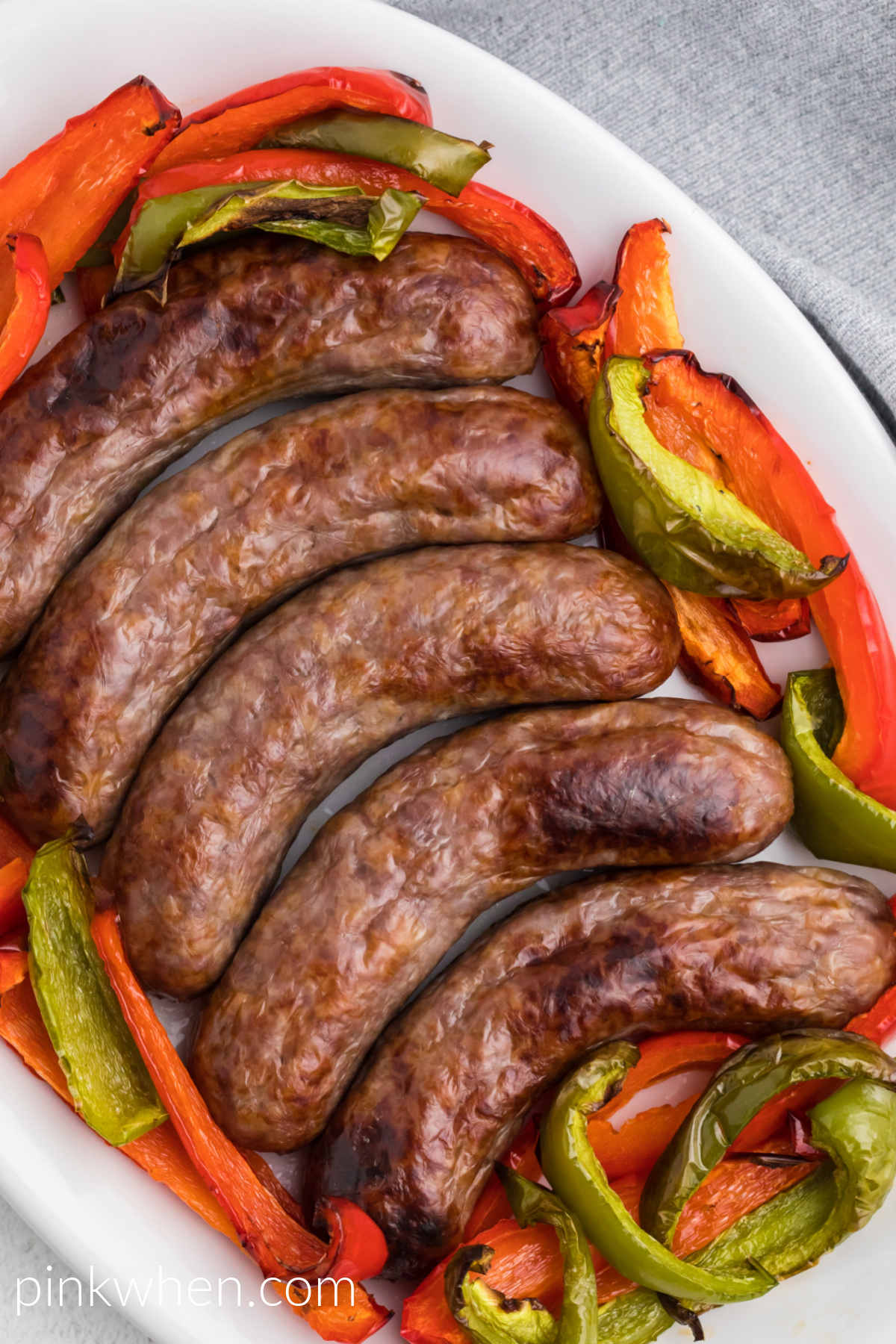 Brats made in the air fryer with bell peppers - served on a white serving dish.