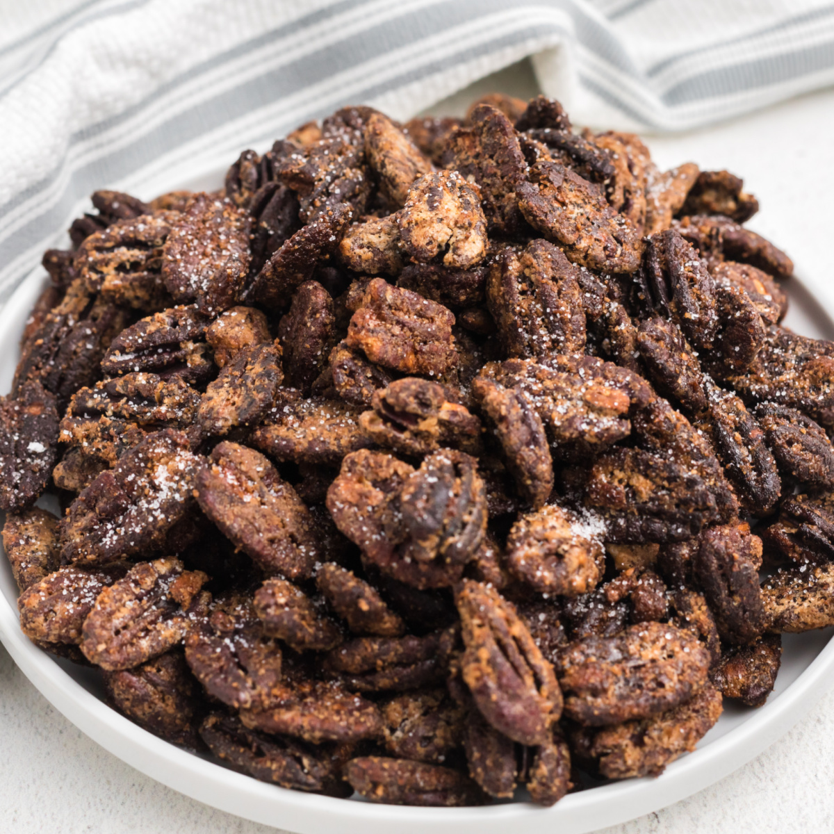Candied pecans made in the air fryer served on a white plate.