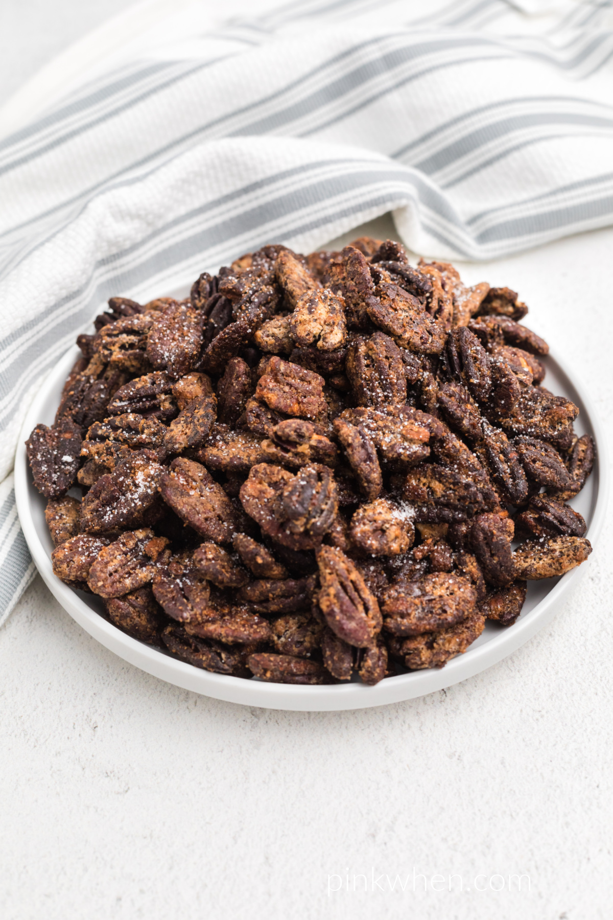 Candied pecans made in the air fryer, on a white plate ready to eat.