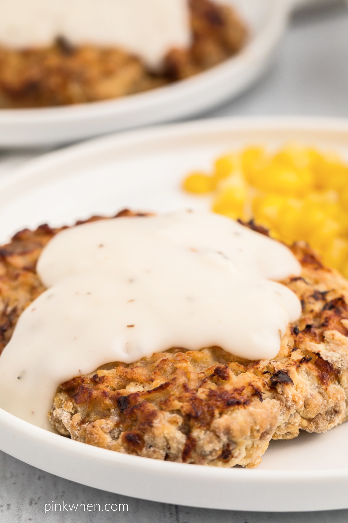 Air Fryer Chicken Fried Steak with white gravy and a side of corn on a white plate.