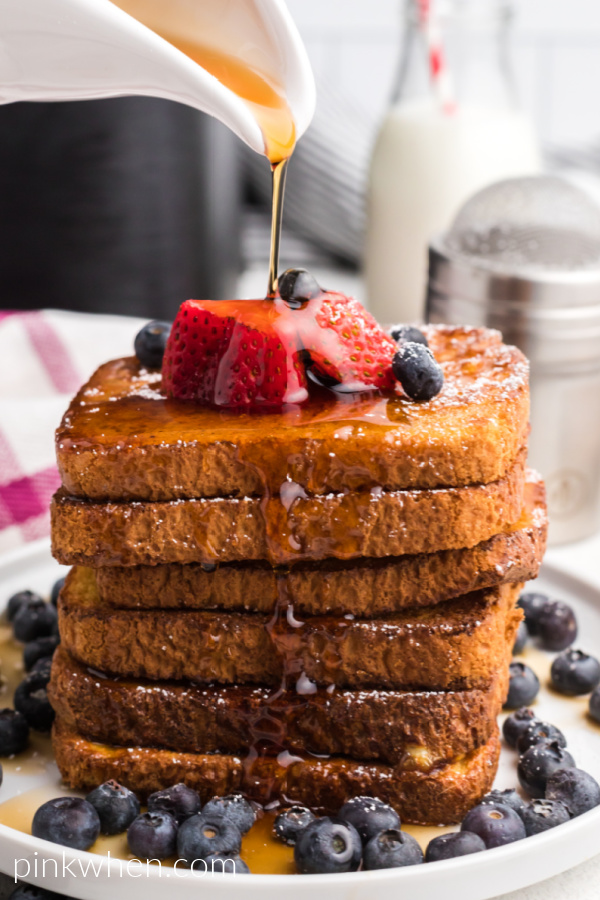 Stack of Air Fried French Toast with fresh berries on a white plate topped with confectioners' sugar and having maple syrup poured on top.