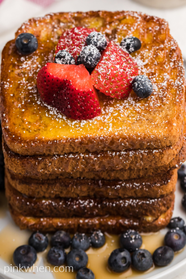 Air Fried French Toast topped with fresh strawberries, blueberries, confectioners' sugar, and real maple syrup.