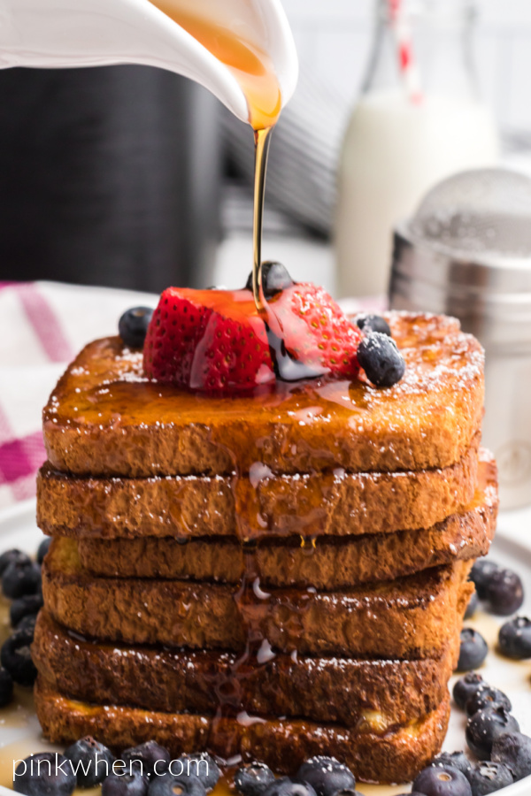 French Toast topped with fresh fruit, confectioners' sugar, and being topped with real maple syrup.