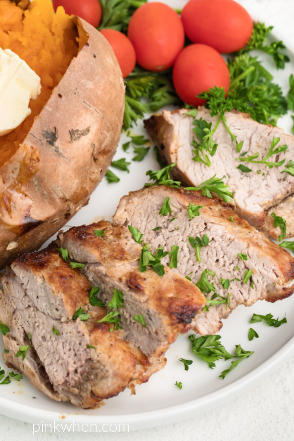 Pork tenderloin on a white plate served with a sweet potato and garnished with fresh chopped parsley.