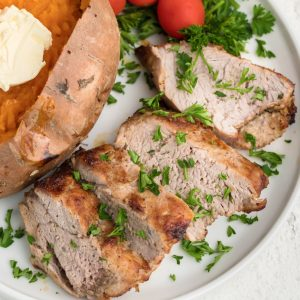 Air Fryer Pork Tenderloin on a white plate and garnished with fresh parsley.